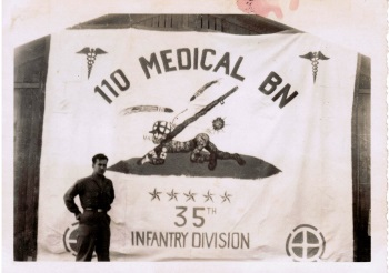 Gene Giordano with 110 Medical Bn Banner he made august 1945